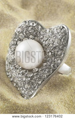 Pearl and diamond silver heart ring on the sand.