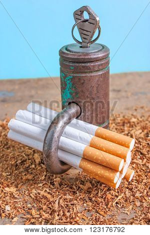 Antismoking background with broken cigarettes, tabacco and a padlock on blue background vertical