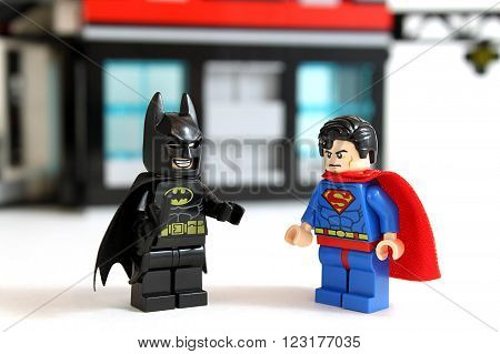 Colorado, USA - March 22, 2015: Studio shot of minifigures Batman and Superman with building in background, image isolated on white.