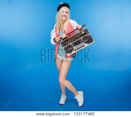 Full length portrait of a smiling female teenager holding retro boom box on blue background