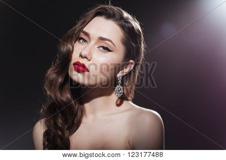 Beauty portrait of a young attractive woman looking at camera over black background