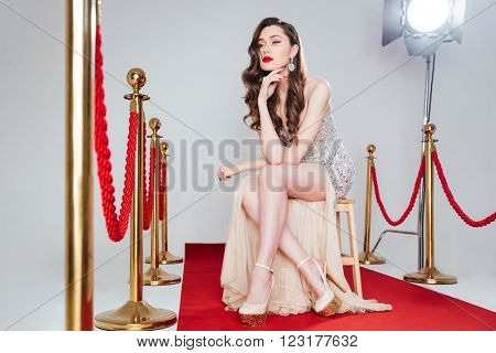 Pensive woman sitting on the chair on red carpet