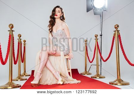 Sexy woman in fashion dress sitting on the chair on red carpet
