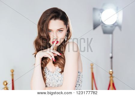 Fashion woman showing finger over lips
