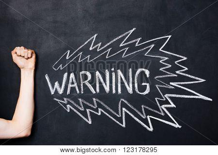 Hand showing fist near warning drawn on blackboard by chalk