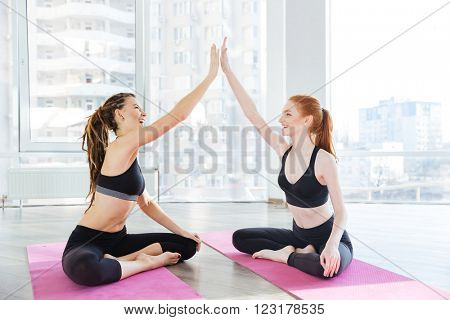 Two cheerful young sportswomen sitting and giving high five after training