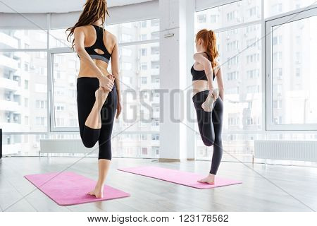 Back view of two attractive young women standing and stretching legs on pink yoga mat