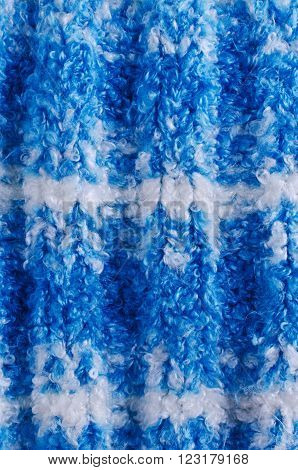 Background of blue handmade knitwear. Selective focus.