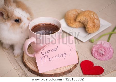 Baby rabbit on table during breakfast. Tea cup, message letter, ranunculus flowers and cookies on the plate.