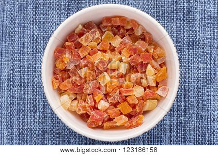 High angle directly above white bowl filled with diced cubes of dehydrated Carica papaya on blue fabric placemat