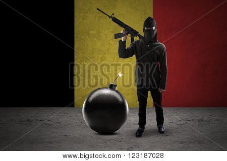 Image of armed terrorist wearing mask and standing near a big bomb with Belgian flag background