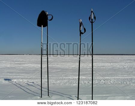 Two pairs of ski poles and wool hat on top of the snow-covered sea ice.