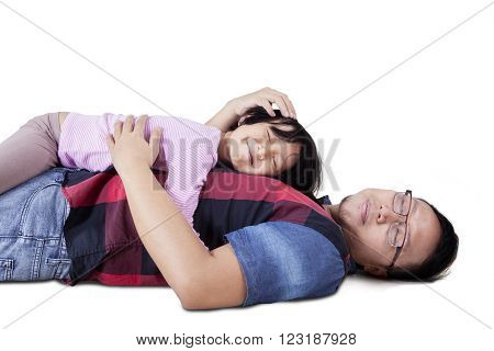 Portrait of a young father lying on the floor while caress his daughter, isolated on white background