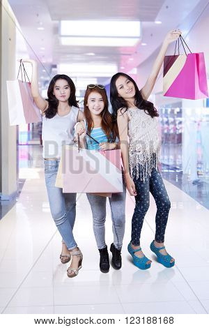 Three teenage girls smiling happy while holding shopping bags in the shopping center