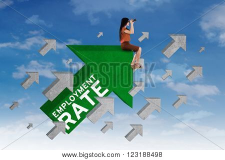 Portrait of female job hunter sitting on the upward arrow sign while using binoculars to look at the sky