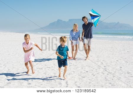 Happy family running at beach with kite. Family enjoying kite flying day at beach. Young smiling family playing at seaside.