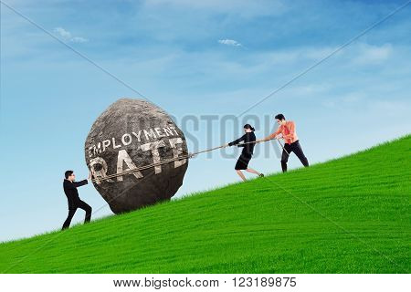 Group of three business people pulling a rock with employment text shot outdoors