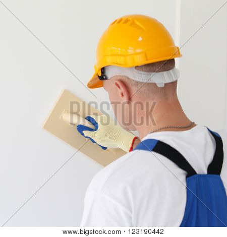 Male plasterer in uniform polishing the wall