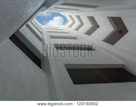 deep atrium gray building overlooking the blue sky with clouds