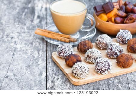 Assorted dark chocolate truffles with cocoa powder, sesame seeds and cup of Cappuccino
