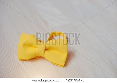 Yellow Bow Tie On Light Wooden Background