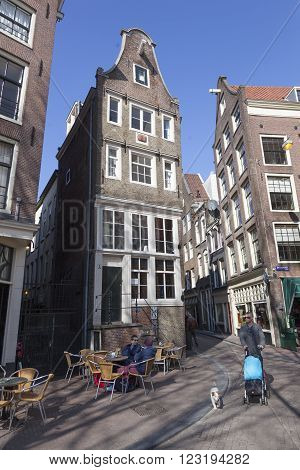 Amsterdam, Netherlands, 17 march 2016: man with dog and child passes terrace in amsterdam red light district on sunny day in spring