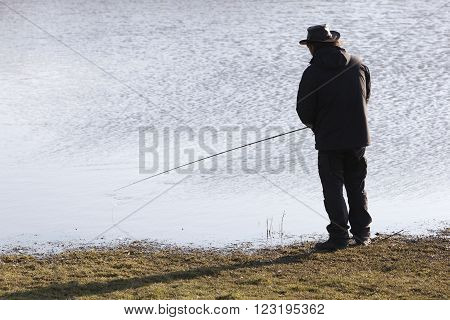 silhouette of lonely fisher with fishong rod near water