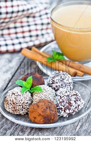 Assorted dark chocolate truffles with cocoa powder and sesame seeds with cup of Cappuccino
