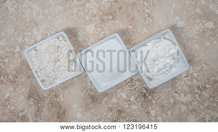 Flour Sugar and Corn Starch in Bowls on a travertine background