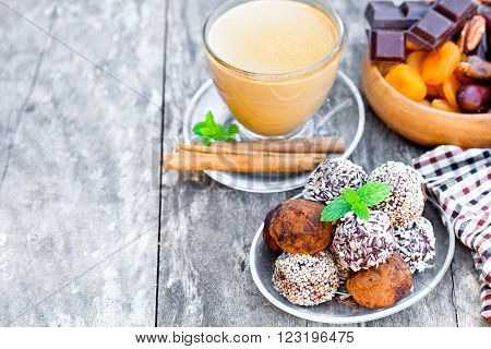 Assorted dark chocolate truffles with cocoa powder and sesame seeds and cup of Cappuccino