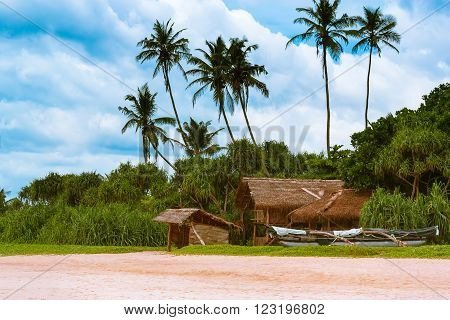 The hut of bamboo and fishing boats on the beautiful sandy beach on the island of Sri Lanka