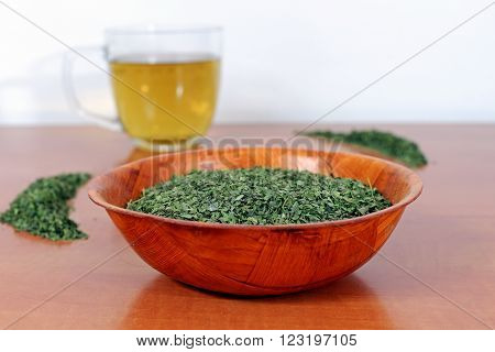 Dried nettle in a wooden bowl with a cup of nettle tea on a wooden table