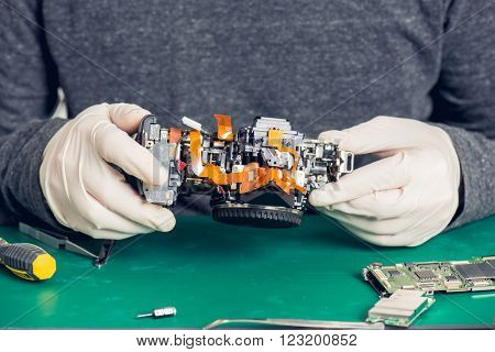 Close up hands of a service worker in gloves repairing digital camera
