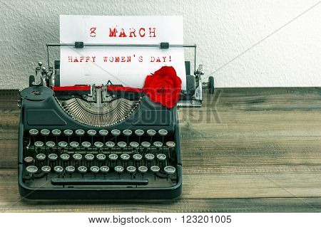 Happy Womens Day! Vintage typewriter with white paper page and red rose flower