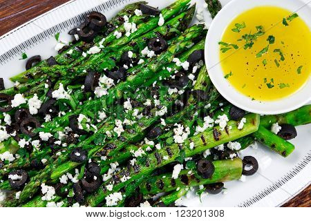 Grilled asparagus salad with feta cheese, olives and souce.