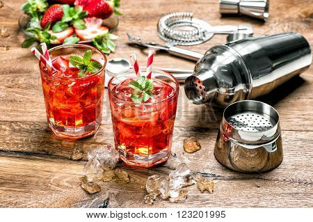 Red drink with ice. Cocktail making bar tools strawberry and mint leaves