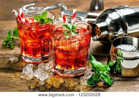 Red drink with strawberry mint leaves ice. Cocktail making bar accessories