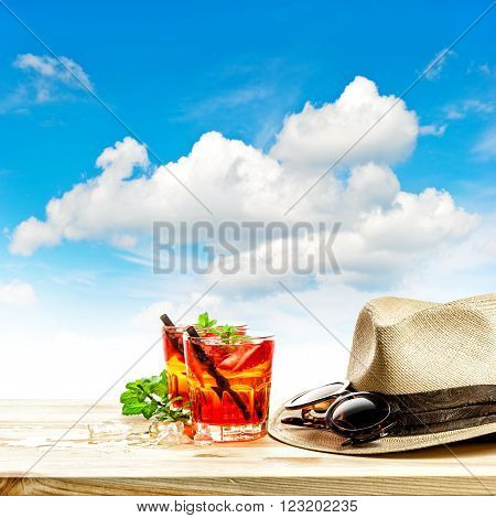 Red tropical drink and green mint leaves. Summer holidays concept with blue sky