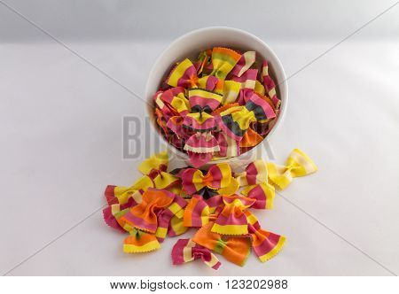 overflowing bowl of colourful pasta bows against a white background