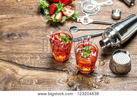 Red drink with ice. Cocktail making bar tools and shaker