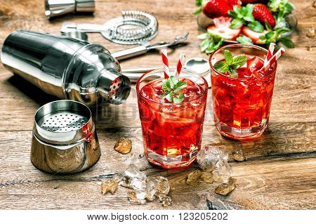 Glass of red drink with ice. Cocktail making bar tools on wooden kitchen table