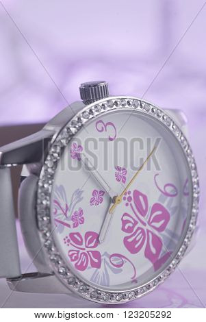 Silver, white, pink and purple watch with diamantes on a purple background.