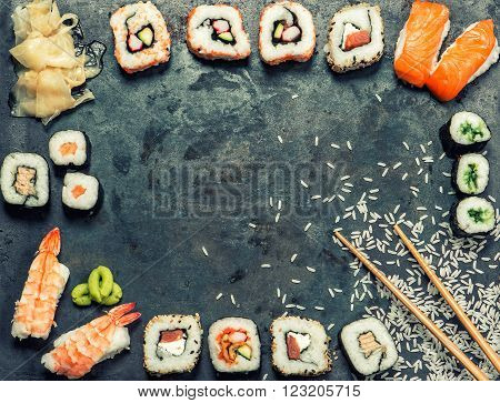 Sushi rolls maki nigiri salmon wasabi shrimp tuna tofu rice avocado pickled ginger. Asian japanese food background. Vintage style toned picture