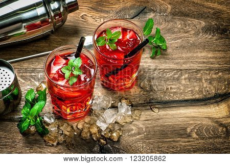 Glasses of red cocktail with ice mint leaves and strawberry on wooden kitchen table. Vintage style toned picture