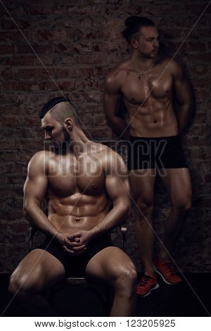 Young muscular men near red brick wall. One is sitting another is standing