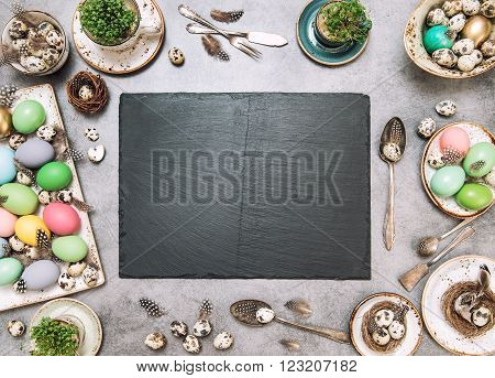 Easter table decoration with colored eggs and stone plate. Holidays background with space for your recipe text