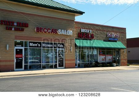 PLAINFIELD, ILLINOIS / UNITED STATES - SEPTEMBER 20, 2015: One may have one's hair cut at Becca's Salon, one's nails trimmed at Becca's Nails, and lunch at Smiley's Restaurant, in a strip mall in Plainfield.