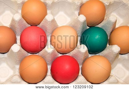 Egg carton with un-dyed organic brown eggs and colourfully dyed Easter eggs.