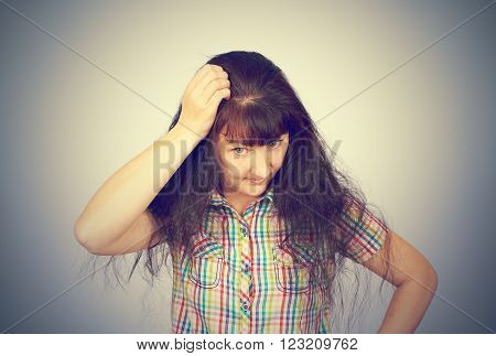 young woman scratching head, thinking daydreaming deeply about something isolated on grey background.