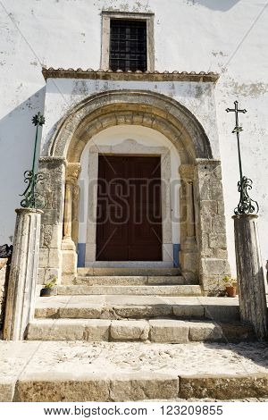 The Romanesque doorway of the Church of Saint Mary with a perfect double arch original imposts and capitals decorated with relief foliage and pecking doves in Torres Vedras Portugal
